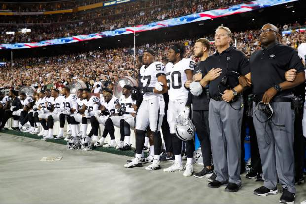 Some members of the Oakland Raiders sit on the bench during the national anthem before an NFL football game against the Washington Redskins in Landover, Md., Sunday, Sept. 24, 2017. (AP Photo/Alex Brandon)