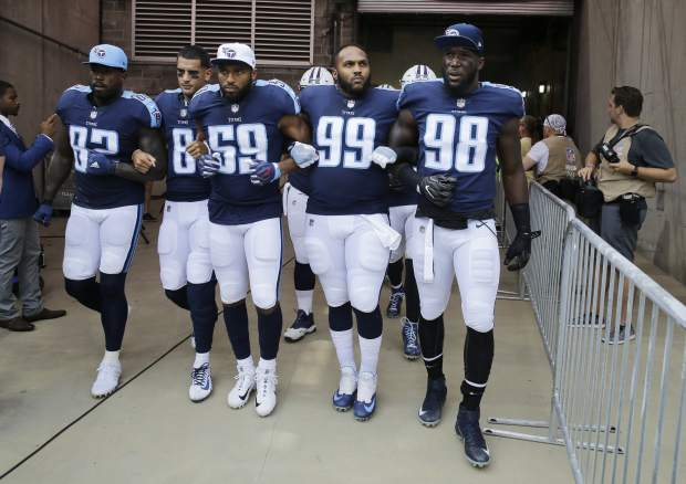 Tennessee Titans players walk to the field with arms linked after the national anthem had been played before an NFL football game between the Titans and the Seattle Seahawks Sunday, Sept. 24, 2017, in Nashville, Tenn. Neither team stood on the field for the anthem. From left are Delanie Walker (82), Marcus Mariota (8), Wesley Woodyard (59), Jurrell Casey (99) and Brian Orakpo (98). (AP Photo/James Kenney)