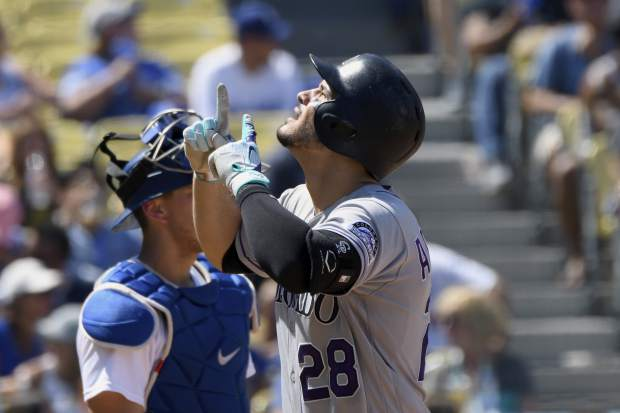 Colorado Rockies' Nolan Arenado points upward as he crosses home plate after hitting a solo home run during the third inning of a baseball game against the Los Angeles Dodgers, Sunday, Sept. 10, 2017, in Los Angeles. (AP Photo/Michael Owen Baker)