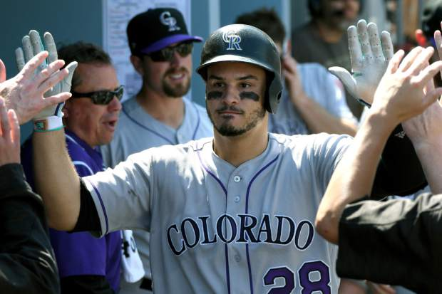 Colorado Rockies' Nolan Arenado (28) is congratulated in the dugout after hitting a solo home run during the third inning of a baseball game against the Los Angeles Dodgers, Sunday, Sept. 10, 2017, in Los Angeles. (AP Photo/Michael Owen Baker)