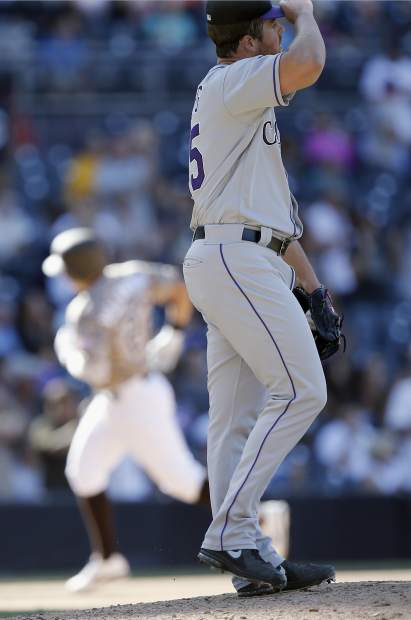 Colorado Rockies relief pitcher Scott Oberg, right, looks away as San Diego Padres' Christian Villanueva rounds the bases after hitting a two-run home run during the sixth inning of a baseball game in San Diego, Sunday, Sept. 24, 2017. (AP Photo/Alex Gallardo)