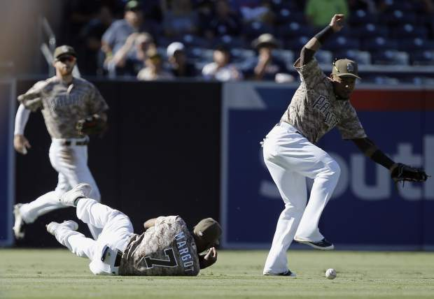 The ball bounces off the glove of San Diego Padres center fielder Manuel Margot, below center, and lands in front of shortstop Erick Aybar, right, for a run scoring double hit by Colorado Rockies' Pat Valaika during the sixth inning of a baseball game in San Diego, Sunday, Sept. 24, 2017. (AP Photo/Alex Gallardo)
