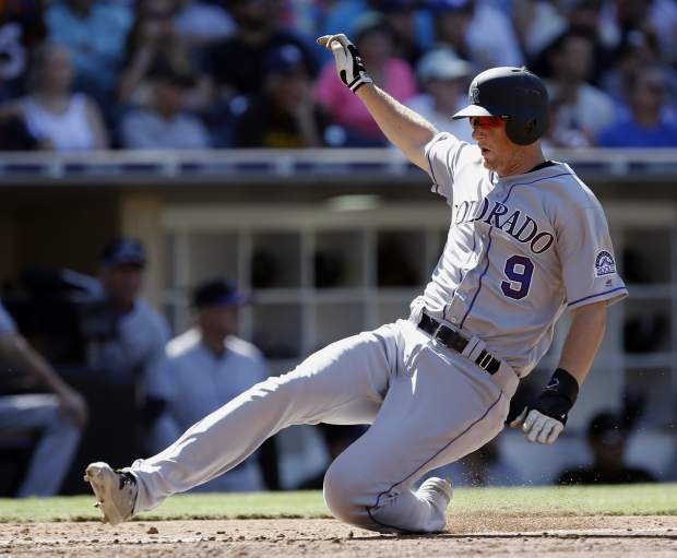 Colorado Rockies' DJ LeMahieu scores on an infield single by Ian Desmond to San Diego Padres third baseman Christian Villanueva during the third inning of a baseball game in San Diego, Sunday, Sept. 24, 2017. (AP Photo/Alex Gallardo)