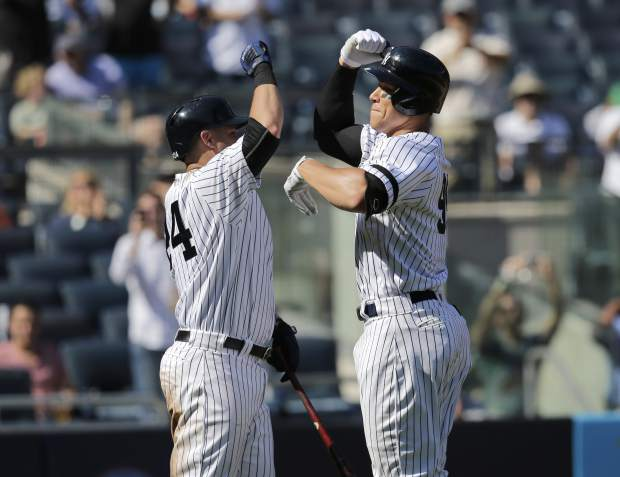 New York Yankees' Aaron Judge, right, celebrates his two-run homer with Gary Sanchez during the third inning of a baseball game against the Kansas City Royals at Yankee Stadium, Monday, Sept. 25, 2017, in New York. It was Judge's 49th home run, which ties the MLB rookie home run record. (AP Photo/Seth Wenig)