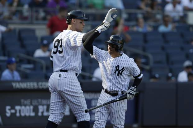 New York Yankees' Ronald Torreyes, right, celebrates scoring a run with Aaron Judge during the eighth inning of a baseball game against the Kansas City Royals at Yankee Stadium, Monday, Sept. 25, 2017, in New York. (AP Photo/Seth Wenig)