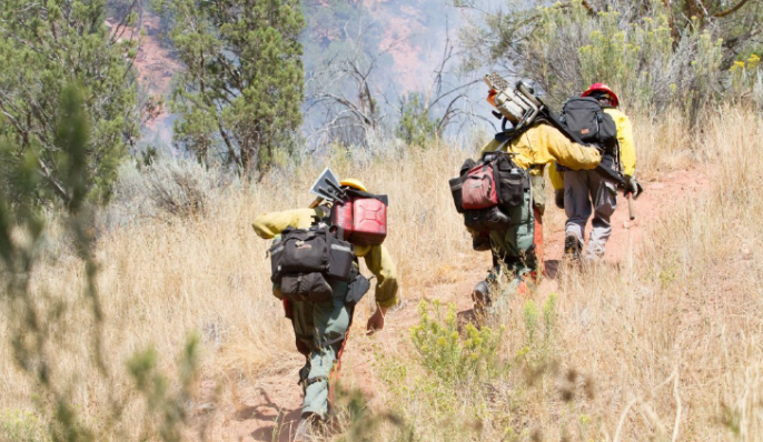 Firefighters head uphill Saturday to the site of a blaze in a homeless camp.