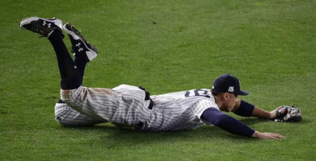 New York Yankees' Aaron Judge makes a diving catch on a ball hit by Houston Astros' Yuli Gurriel during the fifth inning of Game 3 of baseball's American League Championship Series Monday, Oct. 16, 2017, in New York. (AP Photo/Frank Franklin II)