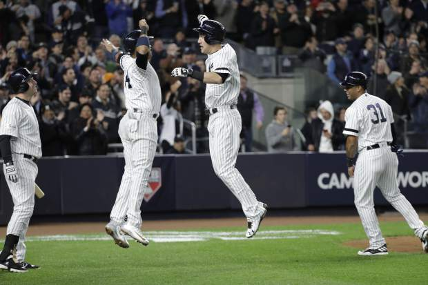 New York Yankees' Todd Frazier celebrates with Starlin Castro after hitting a three-run home run during the second inning of Game 3 of baseball's American League Championship Series against the Houston Astros Monday, Oct. 16, 2017, in New York. (AP Photo/Kathy Willens)
