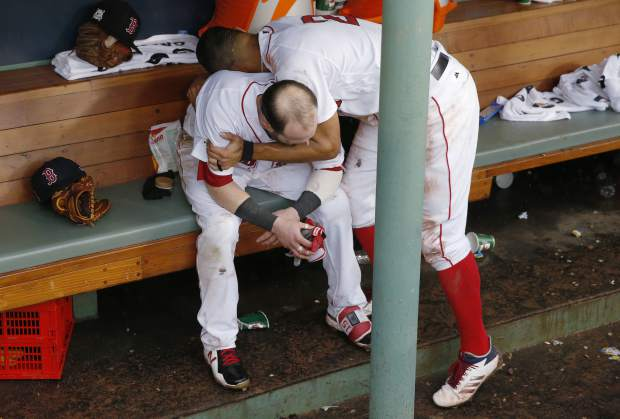 Boston Red Sox's Xander Bogaerts, top hugs Dustin Pedroia in the dugout after the Houston Astros eliminated the Red Sox 5-4 in Game 4 of baseball's American League Division Series, Monday, Oct. 9, 2017, in Boston. (AP Photo/Michael Dwyer)