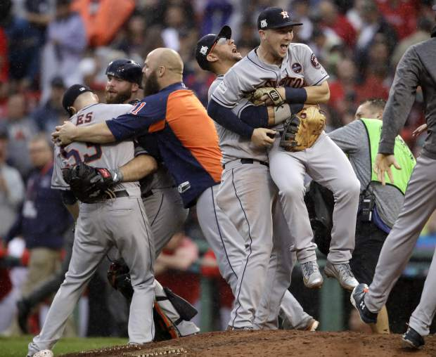 Houston Astros' Yuli Gurriel hugs Alex Bregman, right, as teammates swarm closing pitcher Ken Giles, left, while celebrating their 5-4 win over the Boston Red Sox in Game 4 of baseball's American League Division Series, Monday, Oct. 9, 2017, in Boston. (AP Photo/Charles Krupa)