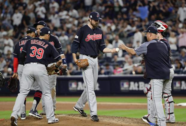 Cleveland Indians pitcher Andrew Miller, center, hands the ball to manager Terry Francona as he leaves the game during the seventh inning in Game 3 of baseball's American League Division Series against the New York Yankees, Sunday, Oct. 8, 2017, in New York. (AP Photo/Frank Franklin II)