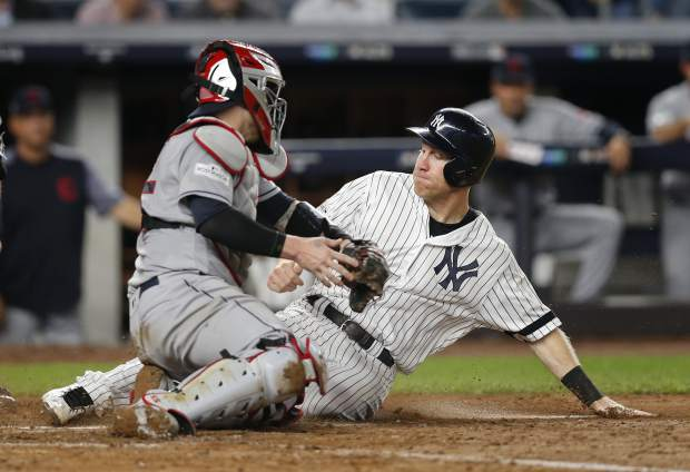New York Yankees' Todd Frazier slides safely into home plate ahead of the tag from Cleveland Indians catcher Roberto Perez on a sacrifice fly by Brett Gardner during the fifth inning in Game 4 of baseball's American League Division Series, Monday, Oct. 9, 2017, in New York. (AP Photo/Kathy Willens)