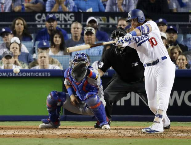 Los Angeles Dodgers' Justin Turner hits an RBI-single against the Chicago Cubs during the fifth inning of Game 2 of baseball's National League Championship Series in Los Angeles, Sunday, Oct. 15, 2017. (AP Photo/Alex Gallardo)