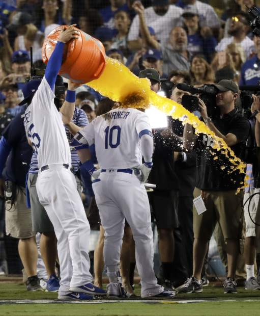 Los Angeles Dodgers' Justin Turner get soaked with sports drink after a three-run walk off home run against the Chicago Cubs during the ninth inning of Game 2 of baseball's National League Championship Series in Los Angeles, Sunday, Oct. 15, 2017. The Dodgers won, 4-1. (AP Photo/Alex Gallardo)