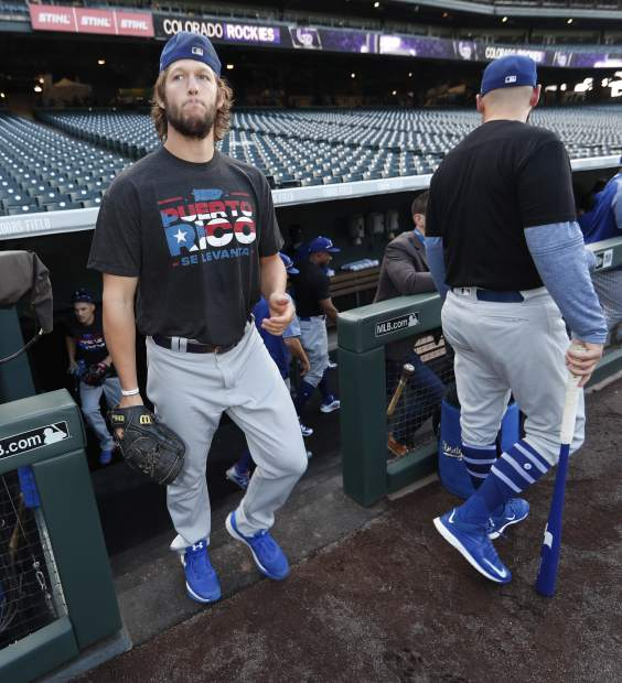 Los Angeles Dodgers starting pitcher Clayton Kershaw wears a Hurricane Maria shirt to rise money for relief efforts in Puerto Rico before a baseball game against the Colorado Rockies, Friday, Sept. 29, 2017, in Denver. (AP Photo/David Zalubowski)