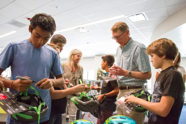 Alpine Bank employee Kent Wilson helps students cut off the tags of their new bike helmets.