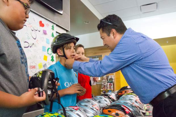 Alpine Bank employee Carlos Jaquez helps Glenwood Springs Middle School seventh-grader Daniel Sanchez try on his brand new bike helmet, which was provided to students by Alpine Bank. Alpine Senior VP Patrick Mckibben responded to last week's Post Independent story about the bike safety assembly at the school by finding a way to provide 150 students with new helmets. At least half of the students at GSMS have been riding their bikes to school during the bridge detour, and of those students, half were riding without helmets.