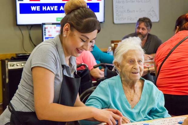 Resident Helen Mattivi and staff member Elizabeth Salgado play bingo together at the E. Dene Moore Care Center in RIfle.