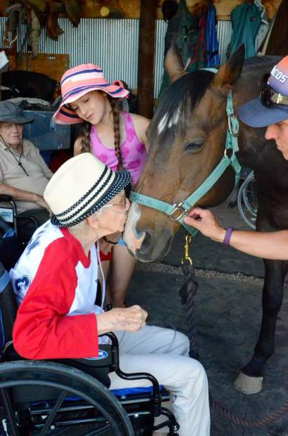 E. Dene Moore resident Lorraine Guy kisses horse Stevie at the R.I.D.E. Program in Silt.