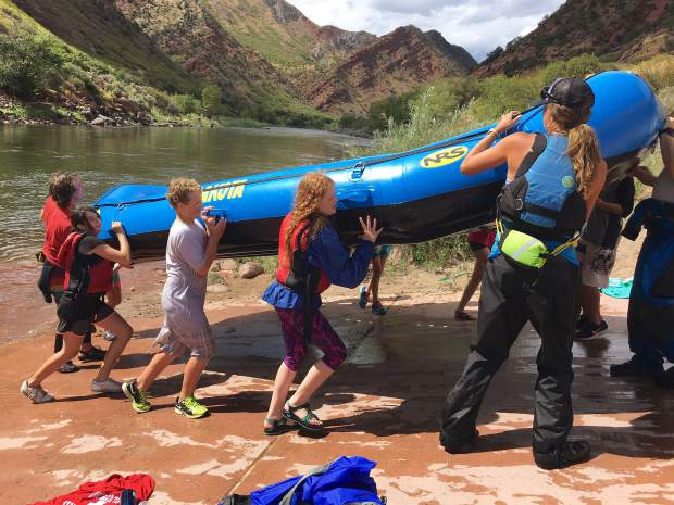 Glenwood Springs Middle School seventh graders work as a team to carry a raft from the water, under the instruction of Glenwood Adventure Co. guides Jenn Cleary, right, and Hayden Knapp, back of the boat.