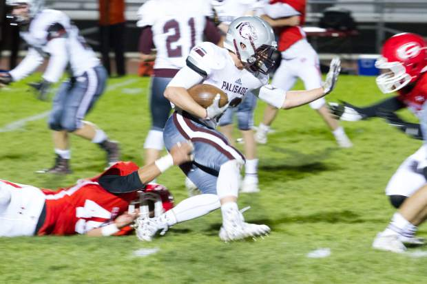 Palisade Bulldog running back Austin Bernal (33) stiff arms the defending Glenwood Springs Demon during Friday night's game at Stubler Memorial Field.