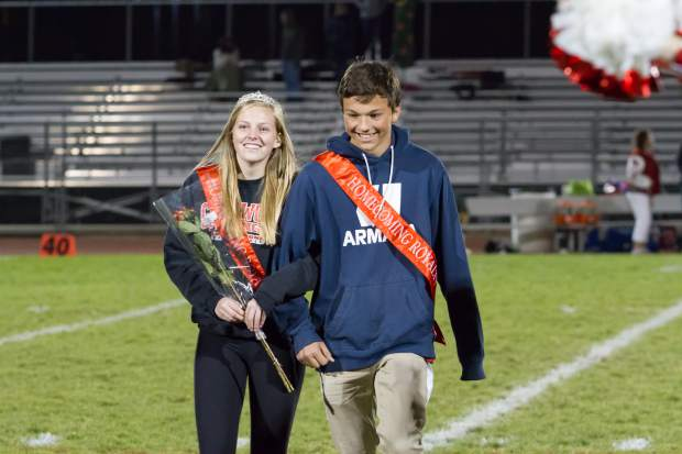 Senior Homecoming royalty Mikey Willis and Josie Spence walk across the field during the halftime show at Friday night's game.