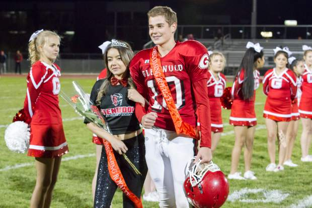 Freshman Homecoming royalty Wheatley Nieslanik and Kimberly Esparza walk across the field during the Homecoming halftime show at Stubler Memorial Field.