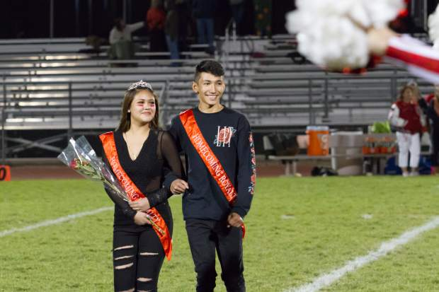 Sophomore Homecoming royalty America Gonzalez and Raul Vargas walk across the field during the halftime show during Friday night's game at Stubler Memorial Field.