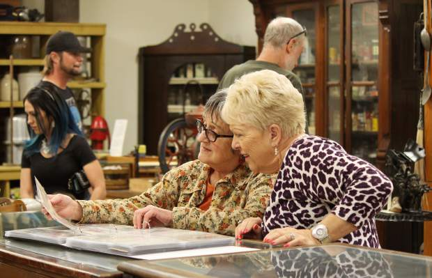 Shirley Lawson, left, and Betty Waldron flip through photos at the Rifle Heritage Center.