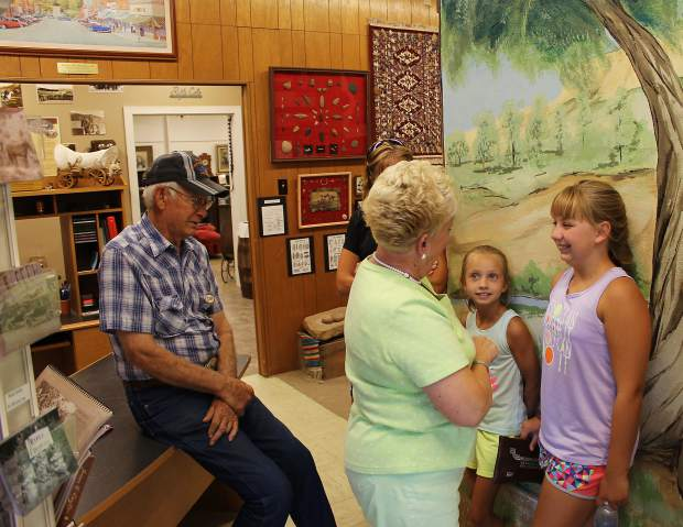 Jadyn Petree, right, flashes a smile to Betty Waldron of the Rifle Heritage Center. Jadyn's sister, Rylan, stands left of her sister, and Cecil Waldron leans against a desk to the far left. Petree remains involved with the center.