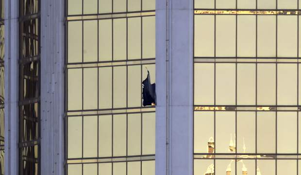 A broken window is seen at the Mandalay Bay resort and casino Monday, Oct. 2, 2017, on the Las Vegas Strip following a deadly shooting at a music festival in Las Vegas. (AP Photo/Chris Carlson)