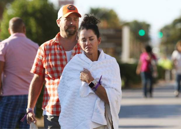 Melissah Burke and her husband Stephen, of Seattle, walk along the Las Vegas Strip near Mandalay Bay hotel and casino Monday, Oct. 2, 2017, in Las Vegas. The couple, who were attending the music festival last night where a mass shooting occurred, found refuge in a nearby apartment and casino. (AP Photo/Ronda Churchill)
