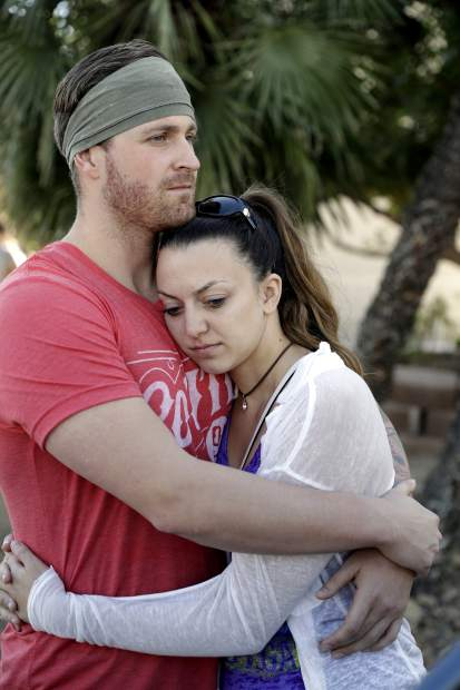 Sean Bean, left, of Livermore, Calif., and his girlfriend Katie Kavetski, of San Leandro, Calif., who both attended a concert where a mass shooting occurred, embrace on the Las Vegas Strip, Monday, Oct. 2, 2017, in Las Vegas. (AP Photo/Marcio Jose Sanchez)