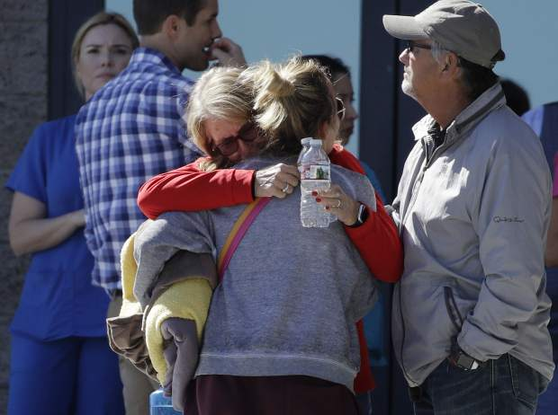 Two women embrace outside of a family assistance center Monday, Oct. 2, 2017, in Las Vegas. The makeshift center was set up to help families and others reconnect after the mass shooting on the Las Vegas Strip. (AP Photo/John Locher)