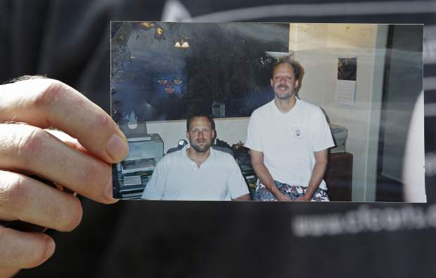Eric Paddock holds a photo of him, at left, and his brother, Stephen Paddock, at right, outside his home, Monday, Oct. 2, 2017, in Orlando, Fla. Stephen Paddock opened fire on the Route 91 Harvest Festival on Sunday killing dozens and wounding hundreds. (AP Photo/John Raoux)