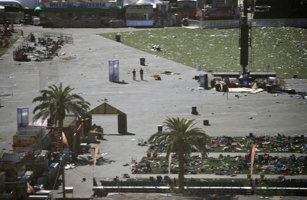 EDS NOTE: GRAPHIC CONTENT - Debris is strewn through the scene of a mass shooting at a music festival near the Mandalay Bay resort and casino on the Las Vegas Strip, Monday, Oct. 2, 2017, in Las Vegas. (AP Photo/John Locher)