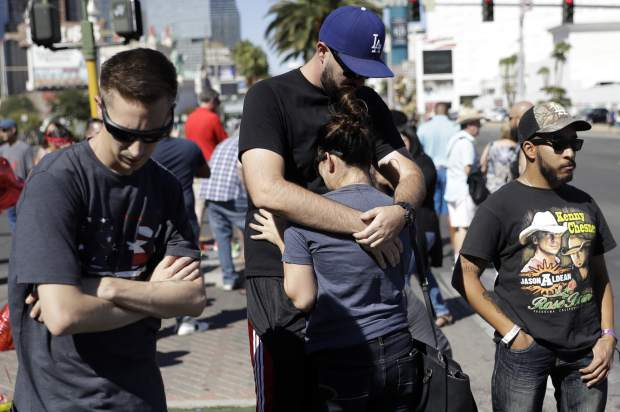 Reed Broschart, center, hug his girlfriend Aria James on the Las Vegas Strip in the aftermath of a mass shooting at a concert Monday, Oct. 2, 2017, in Las Vegas. The couple, both of Ventura, Calif., attended the concert. (AP Photo/Marcio Jose Sanchez)
