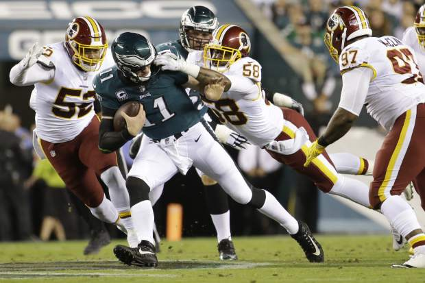 Washington Redskins linebacker Junior Galette (58) grabs at the facemask of Philadelphia Eagles quarterback Carson Wentz (11) during the first half of an NFL football game, Monday, Oct. 23, 2017, in Philadelphia. Galette and the Redskins were penalized for the infraction. (AP Photo/Michael Perez)