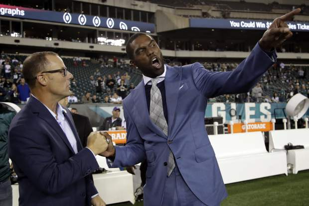 Former Philadelphia Eagles kicker David Akers, left, talks to former NFL wide receiver Randy Moss prior to an NFL football game between the Eagles and the Washington Redskins, Monday, Oct. 23, 2017, in Philadelphia. Prior to the game, Akers signed a ceremonial contract to retire as an Eagles player. (AP Photo/Michael Perez)