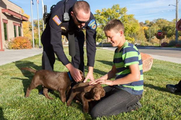 Rifle officer Jared Bartunek and 12-year-old Carter Fulk play with the new puppies that will soon be part of the Rifle Police Department K-9 unit.