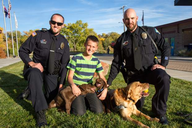 From left to right, Rifle officer Jared Bartunek, new puppies Jax and Makai, 12-year-old Carter Fulk, RIfle police canine Tulo and Rifle officer Garrett Duncan.