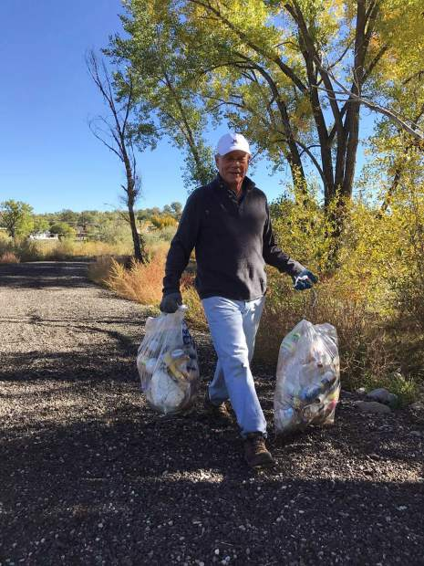 Grant Fiedler carries trash bags that he and fellow volunteers filled during the clean up. Middle Colorado Watershed Council community outreach  coordinator Annie Whetzel said that the clean up got around 20-30 volunteers this year.