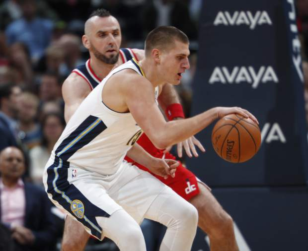 Denver Nuggets center Nikola Jokic, front, of Serbia, fields a pass as Washington Wizards center Marcin Gortat, of Poland, defends in the first half of an NBA basketball game, Monday, Oct. 23, 2017, in Denver. (AP Photo/David Zalubowski)