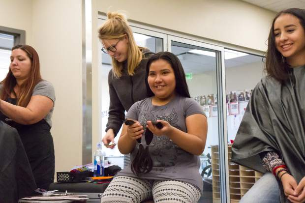 Nine-year-old Andrae Ortiz holds her two locks of hair after donating to Pantene Beautiful Lengths on Friday afternoon.