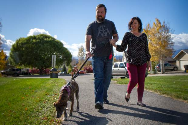 Angela Kay and Kyle Mills take their new puppy Phoebe on a walk near their home in Silt.