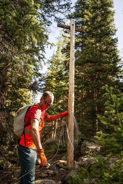 Jaywalker Lodge employee Lynn Sanson coils wire on Independence Pass from telephone poles on Thursday morning near Lincoln Creek.
