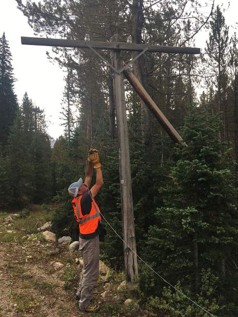 Independence Pass Foundation volunteer pulls tension wire off a telephone pole on Independene Pass this fall. The line was decommissioned but the poles and tension wire strands remain.