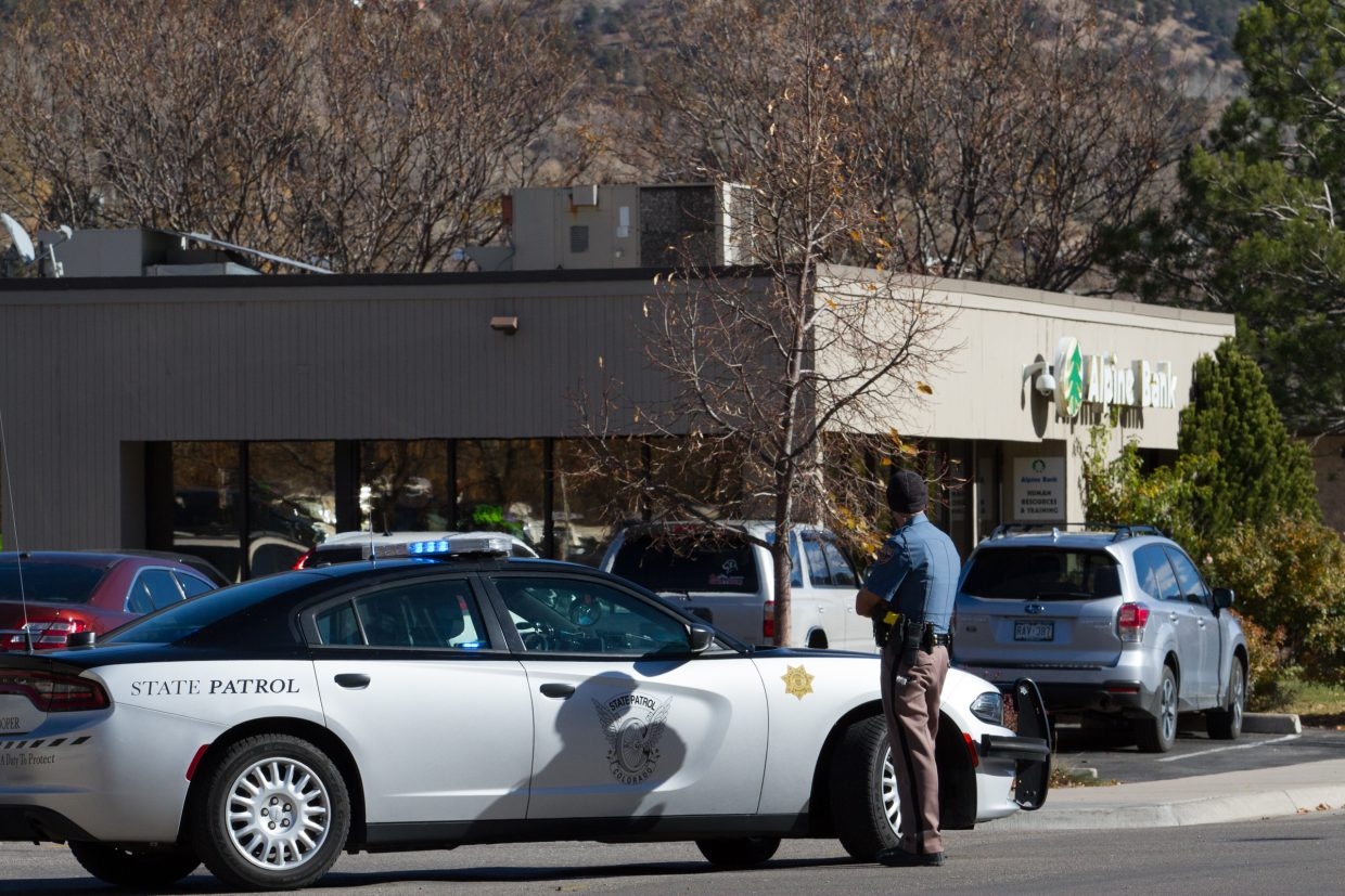 A Colorado State Patrol officer blocks off the street near Highway 6 and Storm King Road after a man left a suspicious package inside the West Glenwood Alpine Bank.