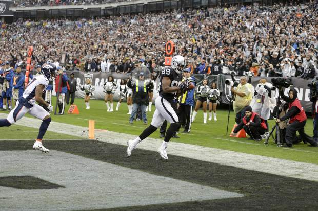 Oakland Raiders wide receiver Amari Cooper (89) catches a touchdown pass in front of Denver Broncos cornerback Brendan Langley (27) during the first half of an NFL football game in Oakland, Calif., Sunday, Nov. 26, 2017. (AP Photo/Ben Margot)