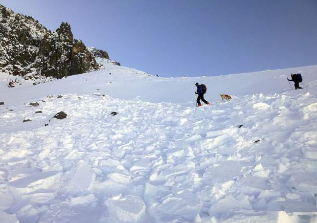 FILE - In this Oct. 9, 2017, file photo provided by the The Gallatin National Forest Avalanche Center, search and rescue volunteers, along with an avalanche dog, search debris in an avalanche field for a missing skier on Imp Peak in the southern Madison Range in southwestern Montana. The body of Inge Perkins was recovered after two skiers triggered the weekend avalanche that fully buried Perkins and partially buried renowned mountaineer Hayden Kennedy. (The Gallatin National Forest Avalanche Center via AP, File)